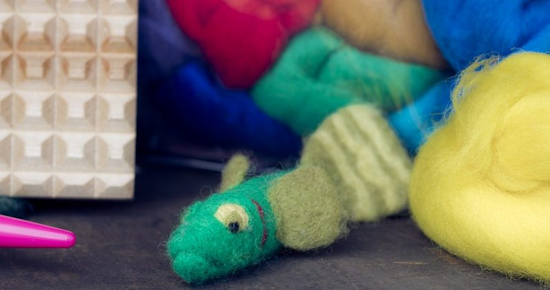 Needle feted fish displayed with felting fiber